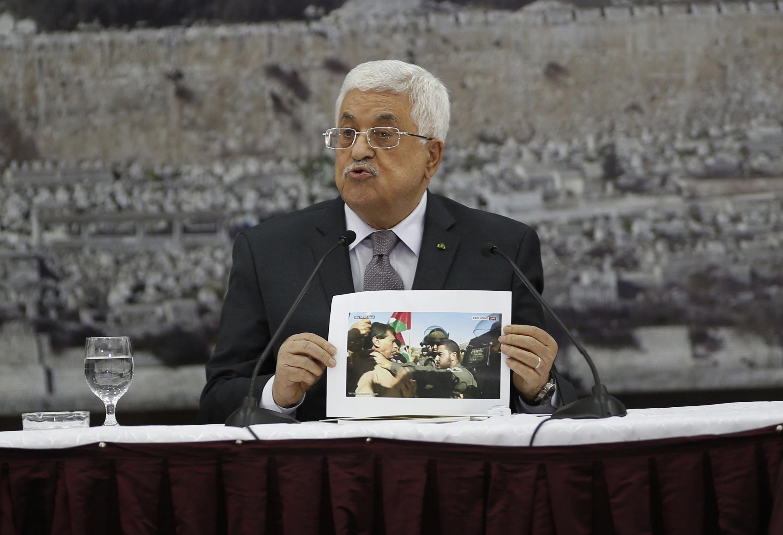 Le président de l'Autorité palestinienne Mahmoud Abbas montrant une photo de Ziad Abu Eïn lors du Comité de direction palestinien réuni, le 10 décembre 2014, à Ramallah.