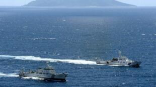 资料图片,中国海监船与日本海上自卫队舰船在中日有主权争议岛屿钓鱼岛(日称尖阁列岛)相遇。摄于2012年9月14日