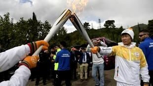 Second torchbearer for Pyeongchang 2018, former South Korean international footballer Park Ji-Sung (R) passes the relay of the Olympic flame near the Temple of Hera in Olympia on October 24, 2017 following the lighting ceremony of the Olympic flame.