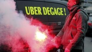 A striking French taxi driver holds a flare during a demonstration in Marseille