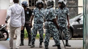 Les forces de l'ordre se tiennent à l'entrée principale d'une résidence où étaient réunie l'opposition comorienne, le 24 mars 2019 à Moroni. Les 12 adversaires du président-candidat se sont réunis pour dénoncer, par avance, les résultats.