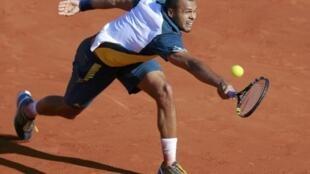 Jo-Wilfried Tsonga hits a return to Roger Federer