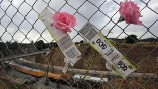 Des fleurs et des étiquettes de bagages sont accrochées à une grille, à proximité du lieu de l'accident.