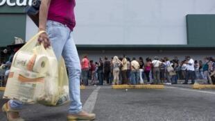 Situation de pénurie. Quand les uns font la queue pendant des heures, les autres peuvent enfin rejoindre leur domicile avant du papier toilette. Caracas, le 4 août 2015.