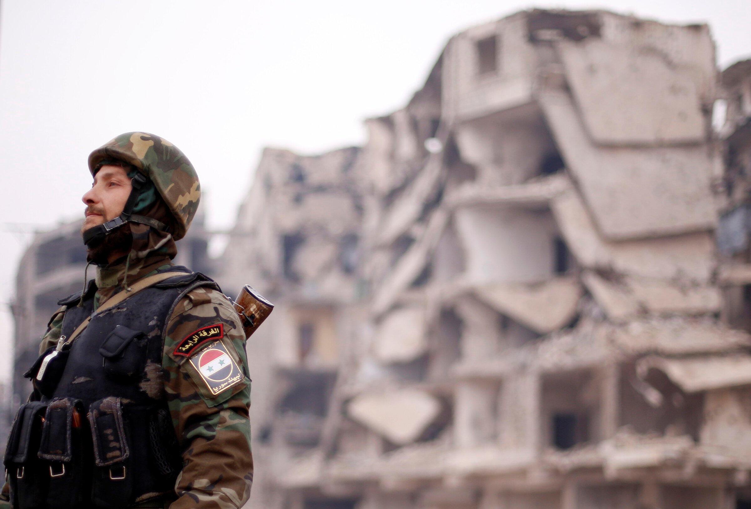 Un soldat de l'armée syrienne devant un bâtiment en ruines d'un quartier d'Alep.