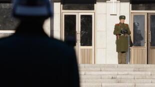 Un soldat de Corée du Nord (à droite) surveillant la frontière coréenne face à un soldat de Corée du Sud (à gauche), dans le village de Panmunjeom.