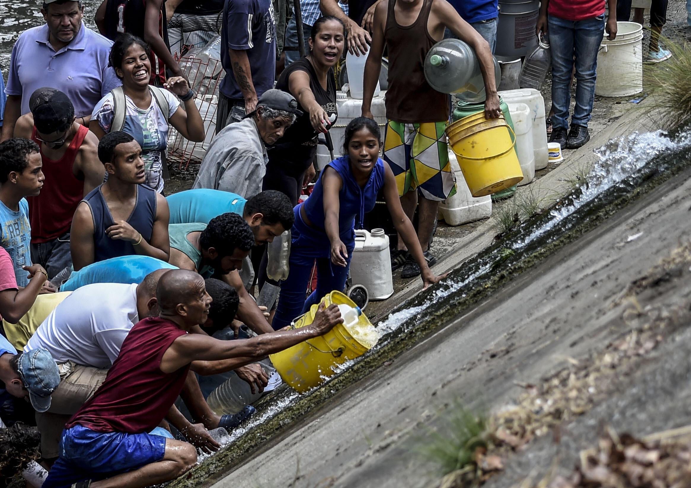 Les habitants vont chercher de l'eau dans un canal d'évacuation des eaux usées de la rivière Guaire, à Caracas, le 11 mars 2019.