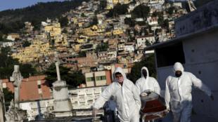 Sepultureros llevan el ataúd de Avelino Fernandes Filho, de 74 años, que murió de la enfermedad coronavirus (COVID-19), durante su funeral en Río de Janeiro, Brasil, el 18 de mayo de 2020. REUTERS/Ricardo Moraes.