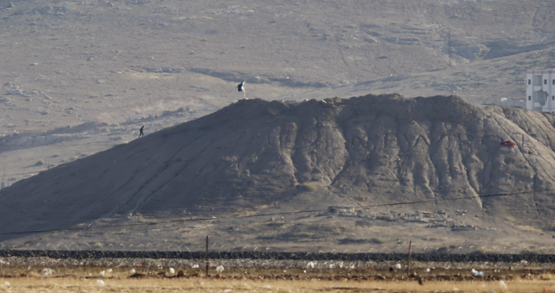 Un combattant islamiste marche près d'un drapeau noir de l'organisation de l'Etat islamique près de la ville syrienne de Kobane, le 6 octobre 2014.