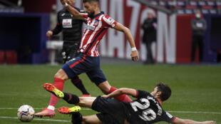 El volante belga Yannick Carrasco, del Atlético de  Madrid, elude al centrocampista del Eibar Unai Dufur (D), en partido de la liga española jugado el 18 de abril de 2021 en Madrid