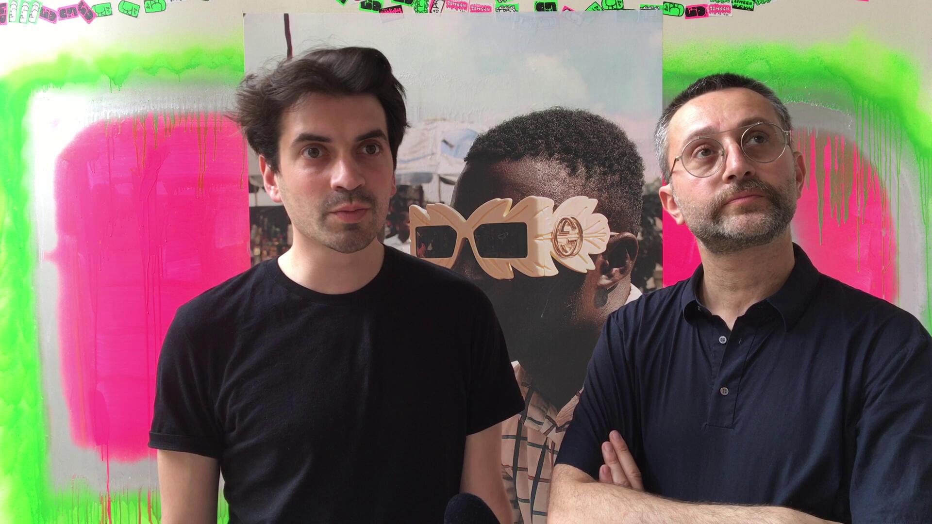 "Curator Hugo Vitrani and associate curator Fabien Danesi, for the exhibition ""Prince.sse.s des villes"", in front of a photo by Stephen Tayo, Okada Boys, Palais de Tokyo, Paris, June 2019"