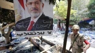 Na capital Cairo, um cartaz de Mohamed Mursi resiste em zona devastada por conflitos entre manifestantes e forças de segurança.