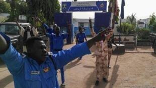 Polícias sudaneses fazem sinal de vitória junto do respectivo quartel general em Cartum a 11 de Abril de 2019.