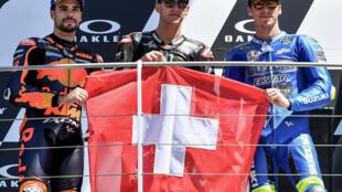 Los pilotos Miguel Oliveira (izq, 2º), Fabio Quartararo (C, ganador) y Joan Mir (3º) suben al podio del Gran Premio de Italia de MotoGP con la bandera suiza en tributo a Jason Dupasquier, fallecido tras el accidente en las clasificaciones de Moto3