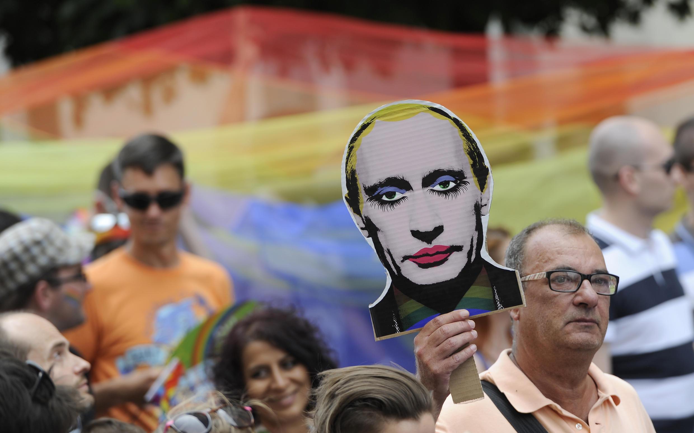 Мужчина держит изображение Владимира Путина на ЛГБТ-параде в Словакии, 28 июня 2014 г.