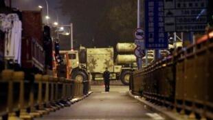 Un véhicule militaire passe au bout d'une rue dans le centre de Pékin, avant le défilé prévu pour le 70e anniversaire de la fondation de la République populaire de Chine.