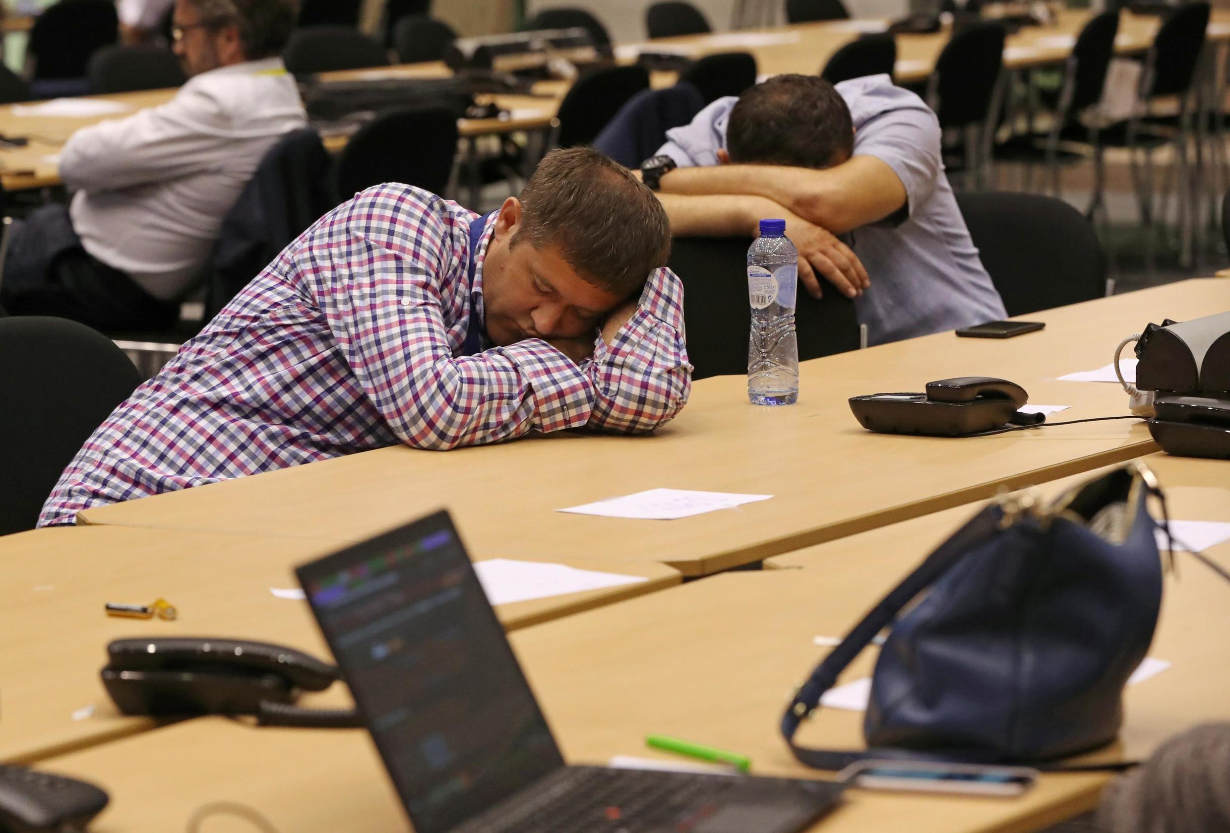 Journalists sleep while waiting for the end of a European Union leaders summit that aims to select candidates for top EU institution jobs, in Brussels, on July 1.