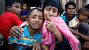 Uma mulher muçulmana Rohingya e seu filho choram depois de serem pegos pela polícia das fronteiras de Bangladesh (BGB) enquanto atravessam ilegalmente um ponto de controle da fronteira em Cox's Bazar, Bangladesh, 21 de novembro de 2016.
