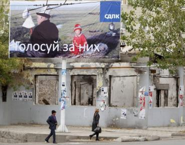 People pass by an election poster in the city of Osh