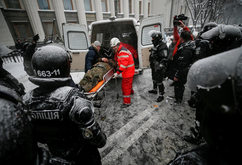 Служба скорой помощи эвакуирует раненого протестующего у здания Рады, Киев, 3 марта 2018 года.