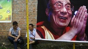 Tibetan men sit next to a portrait of their exiled spiritual leader Dalai Lama during celebrations on his 79th birthday in Kathmandu July 6, 2014.