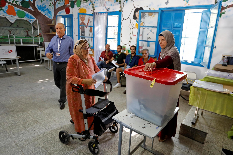 Une femme met son bulletin dans l'urne dans un bureau de vote à Tunis, lors des élections législatives du 6 octobre 2019.
