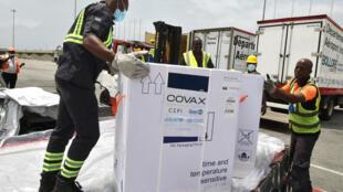 Los trabajadores descargan un contenedor con vacunas de AstraZeneca contra el covid-19 del programa Covax, el 26 de febrero de 2021 en el aeropuerto Felix Houphouet Boigny de Abiyán