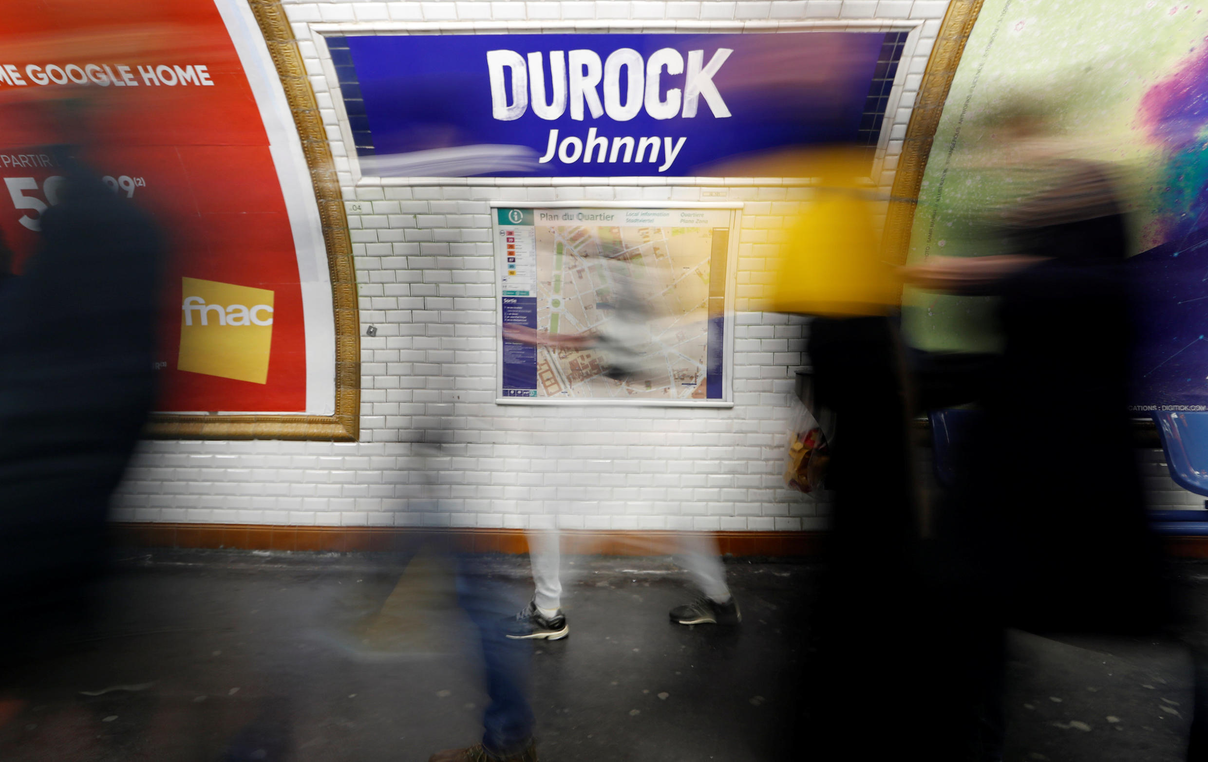 """Commuters walk past a sign which reads, """"DUROCK Johnny"""" on the wall of Duroc metro station in Paris."""