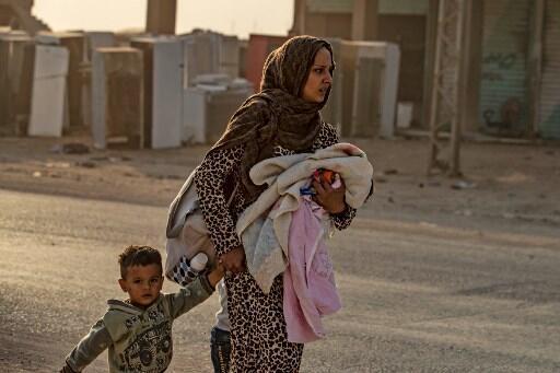 Una mujer y sus hijos huyen de Ras al-Ain, bombardeada por los turcos, el 9 de octubre de 2019.