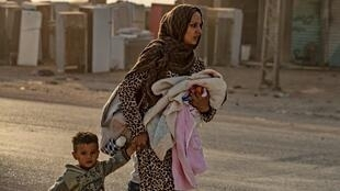 En la ciudad de Ras al-Ain, una mujer y sus hijos huyen de los bombardeos del ejército turco,  9 de octubre, 2019