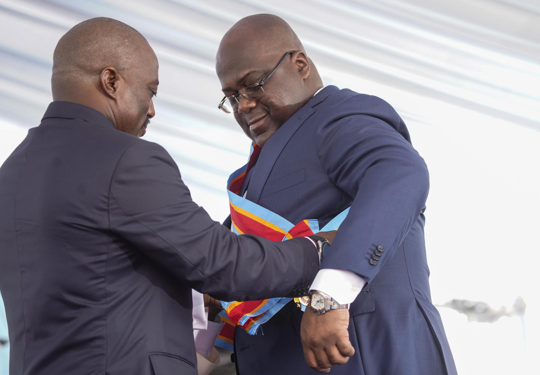 Cérémonie d'investiture du nouveau président de la RDC à Kinshasa, le 24 janvier 2019: le chef d'État sortant Joseph Kabila (G) remet l'écharpe présidentielle à son successeur Félix Tshisekedi (D).