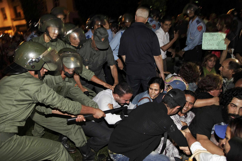 Las fuerzas marroquíes antidisturbios reprimiendo una manifestación en Rabat en protesta por los indultos del rey que dejaron en libertad a un pederasta español.