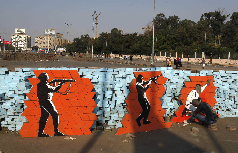 Un supporter de l'ancien président Morsi peint un graffiti sur une barricade protégeant le sit-in des manifestants islamistes.