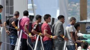 Migrants à leur descente d'un navire militaire italien qui les a secourus en mer, dans le port de Palerme, le 20 août 2015.