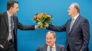 Reiner Haseloff (dcha), primer ministro conservador del estado de Sajonia-Anhalt, entrega un ramo de flores que le entregó el líder de la CDU y máximo candidato del partido para las elecciones generales, Armin Laschet (centro), a Paul Ziemiak, secretario general del partido, el 7 de junio de 2021 en Berlín