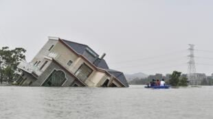 Des habitants chevauchant un bateau devant une maison endommagée et touchée par les inondations près du lac Poyang en raison de pluies torrentielles dans la ville de Shangrao, en Chine, le 15 juillet 2020.