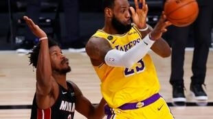 Los Angeles star LeBron James passes the ball as Miami's Jimmy Butler defends during the Lakers' game-four victory over the Heat in the 2020 NBA Finals