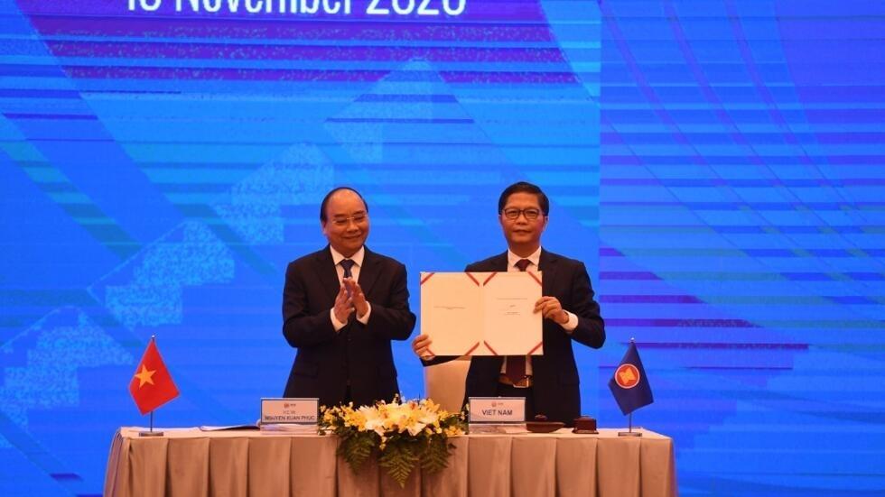 Thủ tướng Việt Nam NGuyễn Xuân Phúc (T) và bộ trưởng Công Thương, Trần Tuấn Anh, trong lễ ký trực tuyến hiệp định RCEP, ngày 15/11/2020.