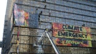 Los bomberos evacuan a los activistas de Greenpeace que colgaron la gran pancarta con el lema 'Emergencia climática' en la fachada del edificio del Consejo Europeo, el 12 de diciembre de 2019 en Bruselas