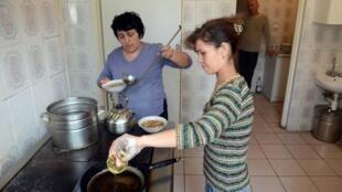 Des réfugiées tatares de Crimée cuisinent pour leur famille, dans un refuge fourni par les autorités ukrainiennes dans le village de Lyubin Welykyi, à 25 km de Lviv, le 22 mars 2014.
