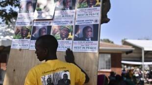 Un villageois fait des collages avec d'anciennes affiches de campagne de Mugabe près du domaine familial de l'ancien leader à Kutama, le 15 septembre 2019.