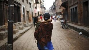 A woman carrying her daughter walks in the streets of the ancient city of Bhaktapur, Nepal