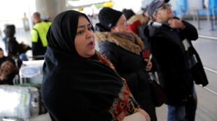 Uma mulher espera a chegada de sua família no aeroporto JFK de Nova York.