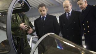 Nicolas Sarkozy (esq.) e o ministro Alain Juppé (centro) observam um Rafale durante visita à base aérea em Saint Dizier.