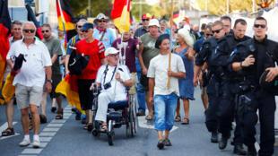 Des manifestants défilent contre la chancélière Angela Merkel lors de sa visite à Dresde, le 16 août 2018.