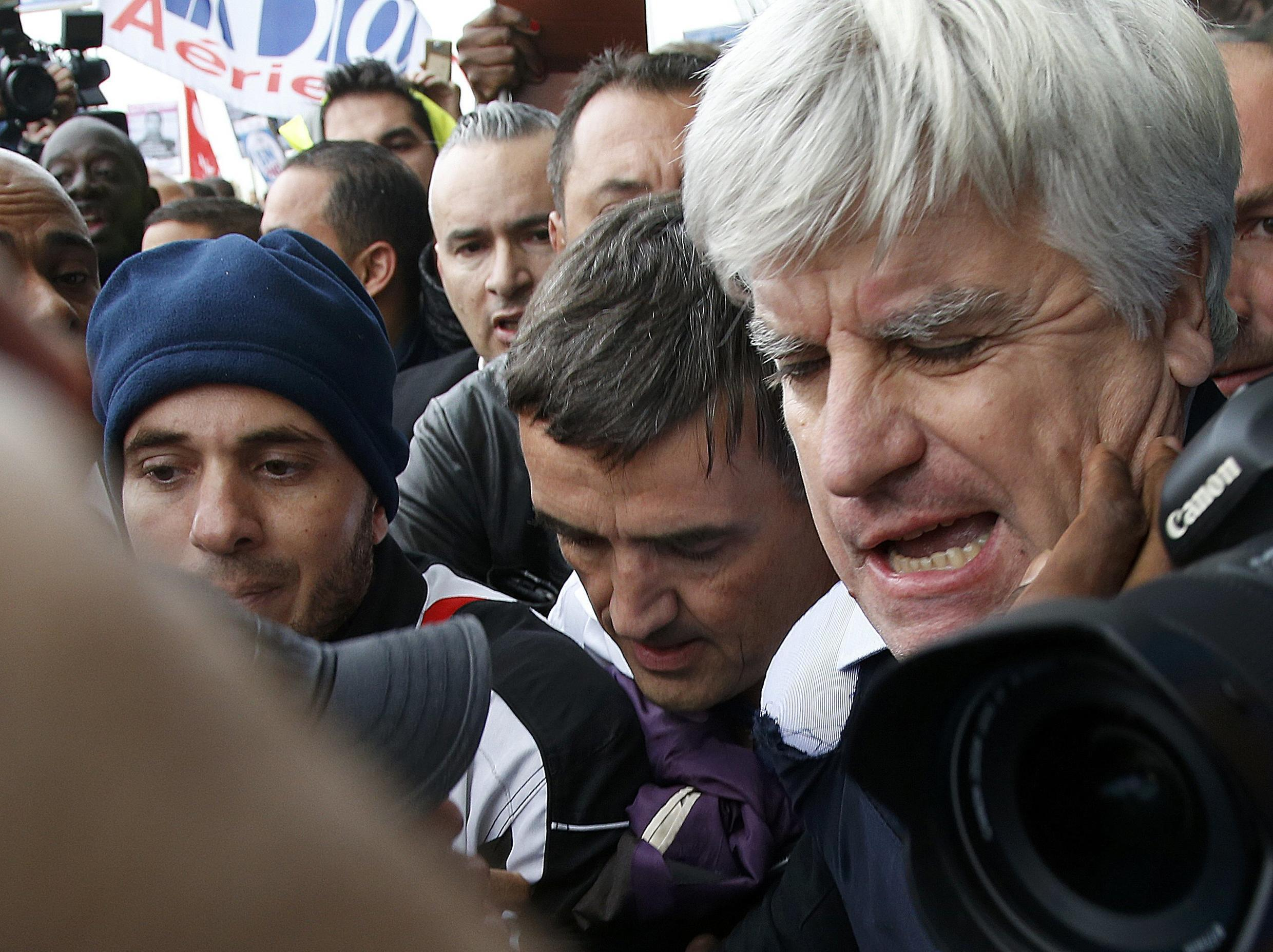 Air France mamangers Xavier Broseta (C) and Pierre Plissonnier (R) surrounded by employees after breakiung off talks with unions