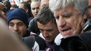 Xavier Broseta (C), Human Resources Manager at Air France, and Pierre Plissonnier (R), Air France deputy of long-haul flights, surrounded by angry employees, October 5, 2015