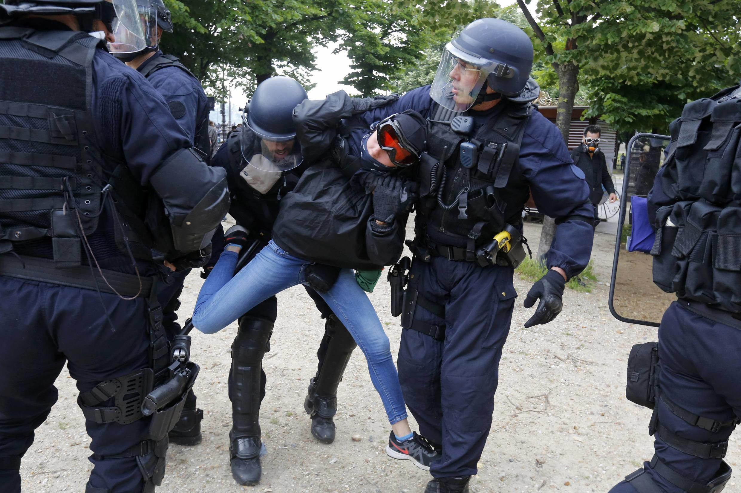 French CRS riot police apprehend a demonstrator during clashes at the Invalides square during a demonstration in Paris as part of nationwide protests against plans to reform French labour laws, France, June 14, 2016.