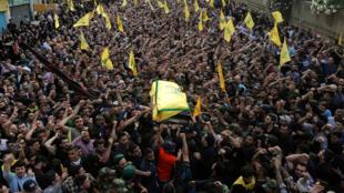 Caixão do ex-comandante militar do Hezbollah na Síria, Mustafá Badreddine, é carregado por uma multidão no sul de Beirute.