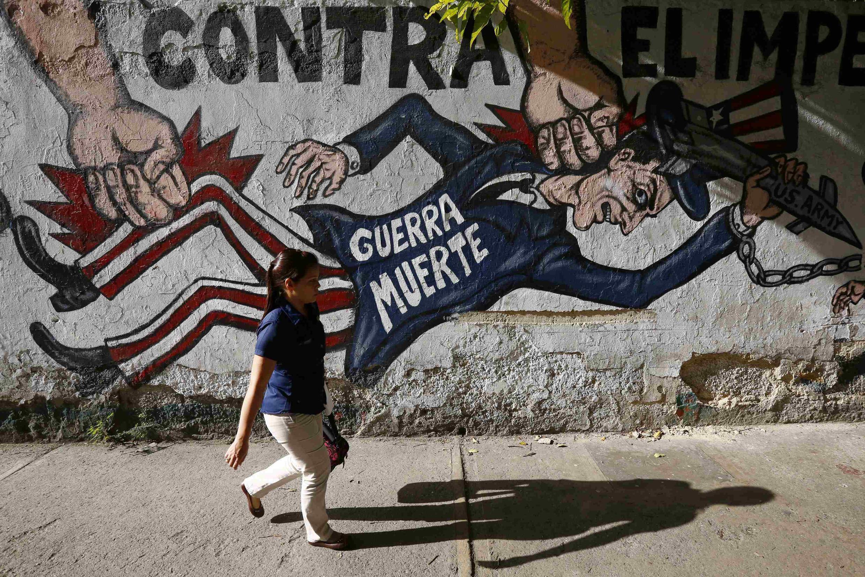 Una mujer pasa indiferente frente a un grafiti anti norteamericano en Caracas, 9 de marzo de 2015